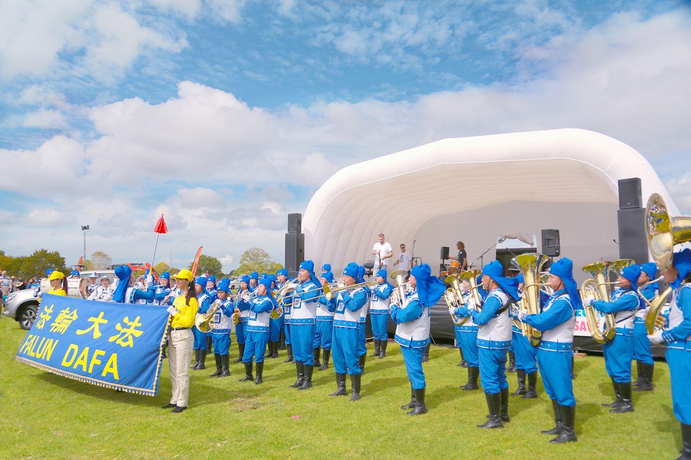 由法輪功學員組成的天國樂團在舞台前表演。(明慧網)