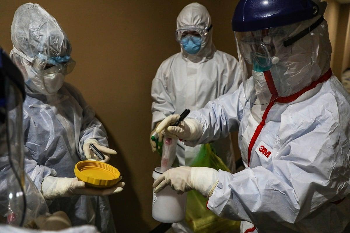 中共聲稱,湖北已連續兩日無新增病例。但多個武漢小區19日又有新增病例,甚至又出現「封樓」現象。圖為一名醫務人員在湖北省武漢的一個檢疫區內採集病毒樣本。(Photo by STR/AFP via Getty Images)