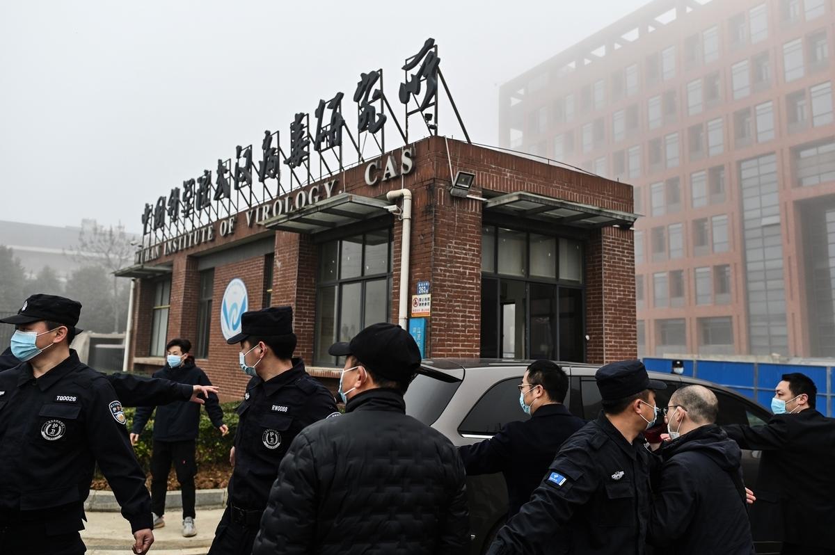 2021年2月3日,世衛專家小組的車隊到達武漢病毒研究所,調查中共病毒的來源。該研究所大門前部署了大量警力嚴密把守。(HECTOR RETAMAL/AFP via Getty Images)