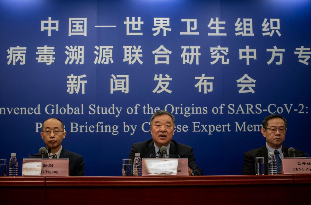 2021年3月31日,中共國家衛生委員會專家組負責人梁萬年(中)與其他中方專家在北京自行召開關於病毒溯源報告的新聞發佈會。(Kevin Frayer/Getty Images)