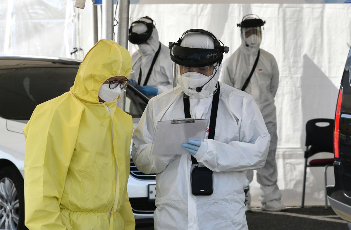 圖為2020年2月29日,南韓醫務人員正在對抗中共肺炎的工作中。(Jung Yeon-je/AFP)