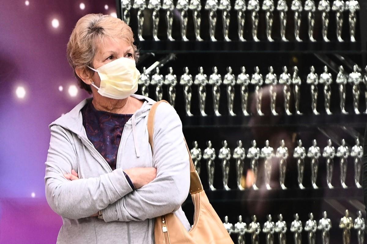 圖為2020年3月10日,一名戴著防護口罩的女士在參觀美國加利福尼亞荷里活的星光大道(Walk of Fame)。(ROBYN BECK/AFP)