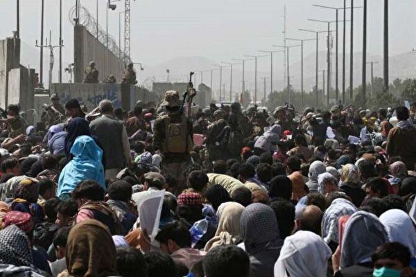 2021年8月20日,在塔利班攻佔阿富汗首都喀布爾後,大批阿富汗人聚集在喀布爾機場附近的路邊,希望能找到機會逃離阿富汗。(WAKIL KOHSAR/AFP via Getty Images)