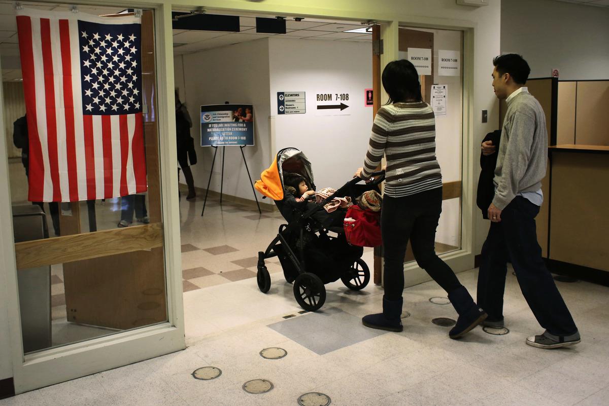 圖:2013年1月29日,中國移民在紐約美國公民和移民服務機構(USCIS)地區辦事處接受面試後帶著他們的孩子離開。(John Moore/Getty Images)