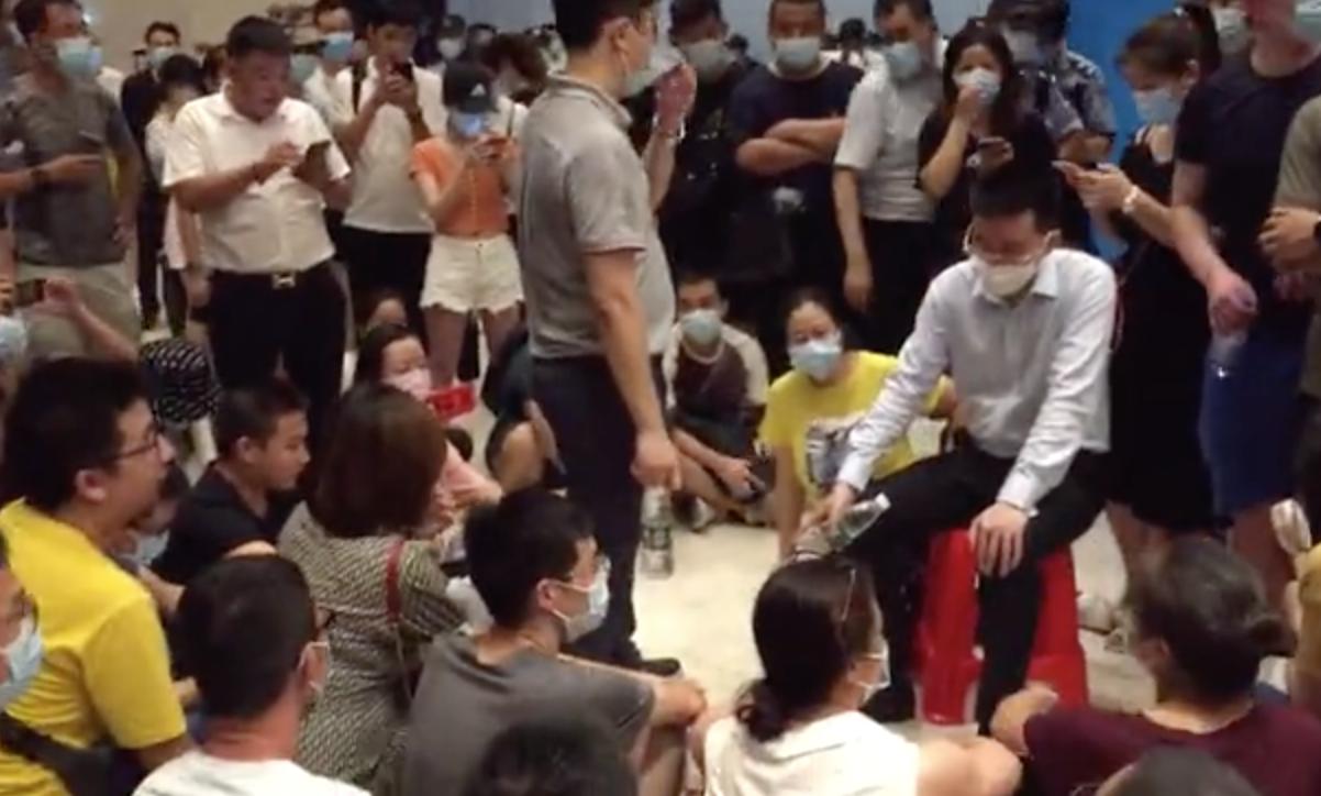 9月12日深夜,恒大深圳總部大廳聚集「恒大財富」商品受害者。(影片截圖)