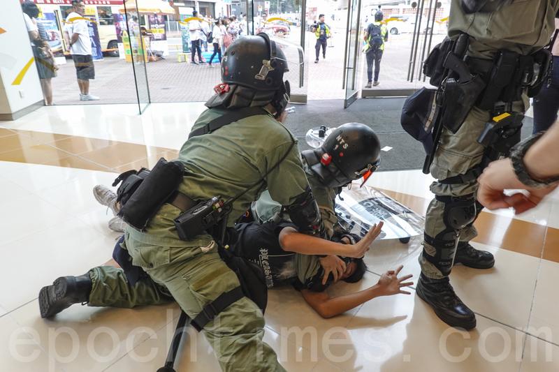 2019年10月13日,港人在18區商場進行「和勇一家 遍地開花」活動。圖為荃灣,防暴警察拘捕示威民眾。(余鋼/大紀元)