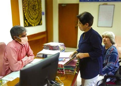 印度法輪功學員給朋迪榭里市教育部門的負責人講法輪功真相。(明慧網)
