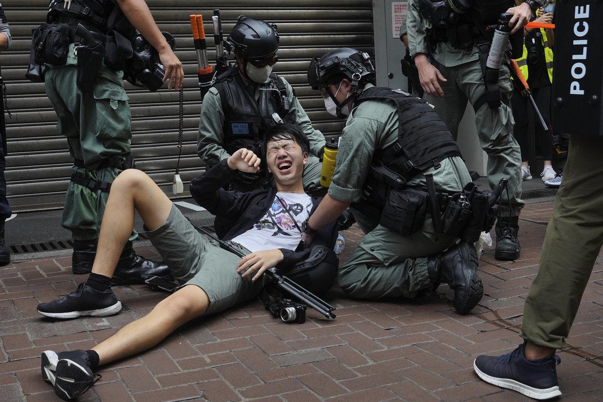 2020年7月1日,香港民眾抗議中共強推「港版國安法」。圖為一抗議者被警察噴辣椒水倒地。(加通社)