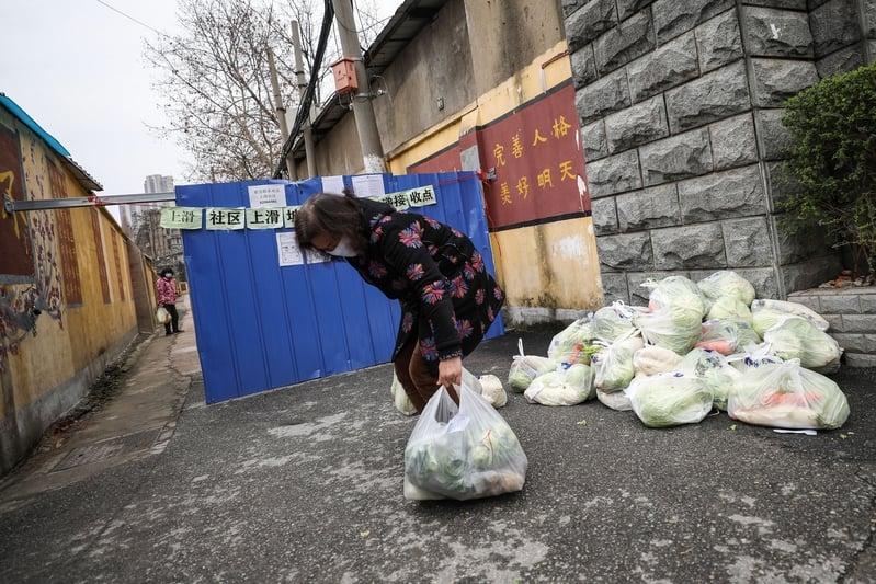 2020年3月3日,湖北省武漢市,一名女子在居民區外拿回網購的食物。(STR/AFP via Getty Images)