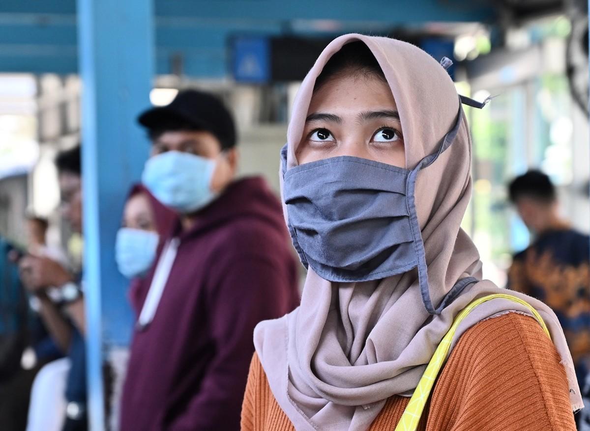 2020年3月2日,一名戴著口罩的婦女站在雅加達的一條街道上。3月2日,印度尼西亞報告了首例確診的中共病毒病例,此前這個世界第四人口大國的衛生官員回擊了針對其明顯缺乏的感染患者的問題。 (ADEK BERRY/AFP)
