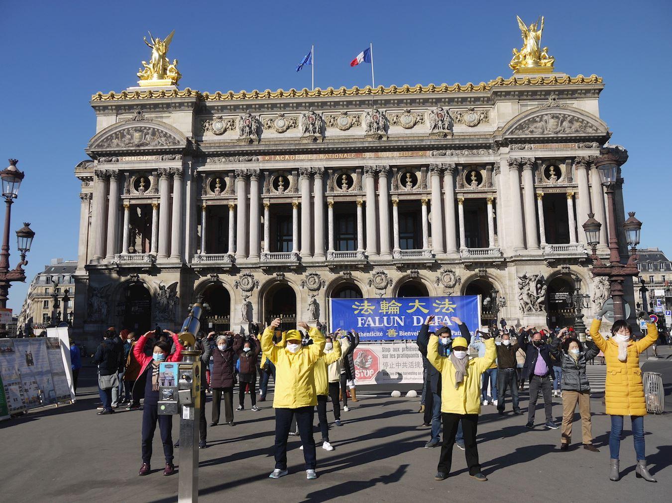 2021年2月28日下午,法輪功學員在巴黎歌劇院廣場舉辦講真相、徵簽活動。圖為法輪功學員演示功法。(明慧網)