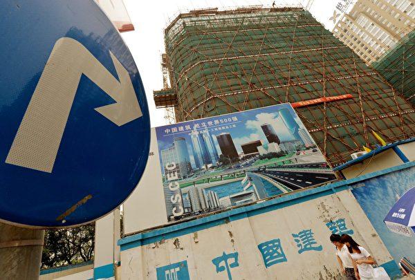 2013年7月26日,上班族走過北京中央商務區的房地產開發廣告牌。中國各地的地方政府對中央組織的對地方債的調查感到擔憂。(Mark Ralston/AFP/Getty Images)