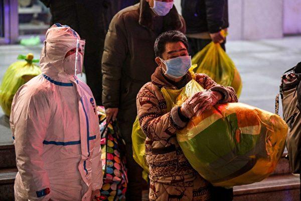 圖為3月3日,習近平訪問武漢期間,武漢感染中共病毒的患者(中)等待從武漢市第五醫院轉移到新建的雷神山醫院。(STR/AFP via Getty Images)