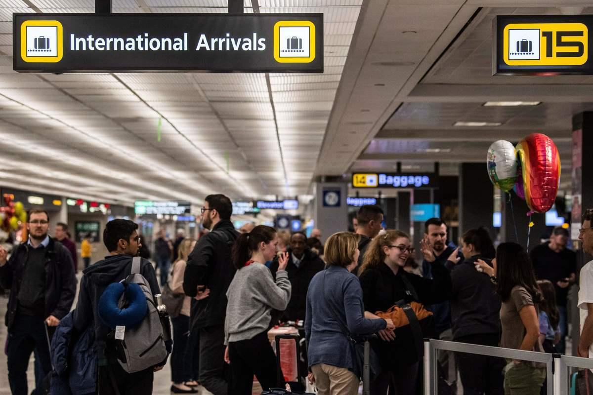 圖為2020年3月13日,美國遊客在華盛頓郊外杜勒斯機場的國際到達區與家人團聚。(ERIC BARADAT/AFP via Getty Images)