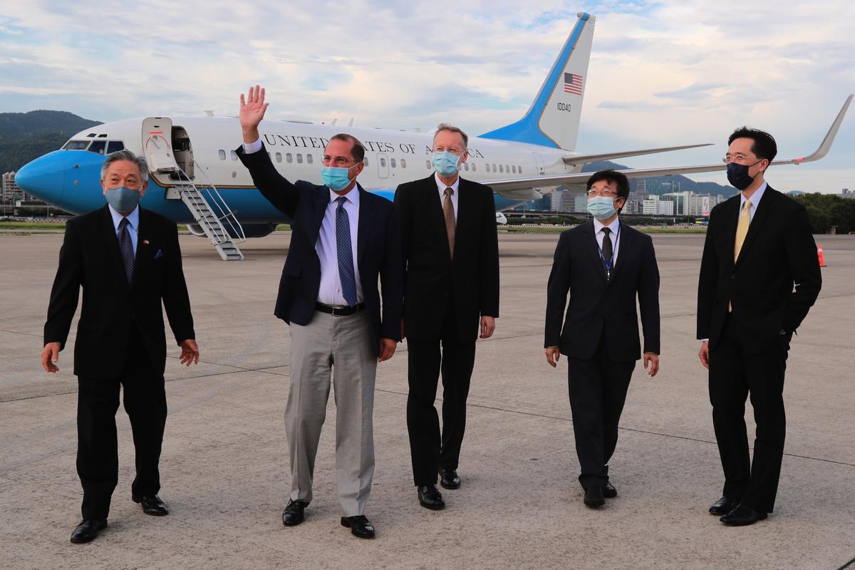 2020年8月9日,美國衛生部長阿扎爾(Alex Azar)(左二)步出軍機,揮手向現場人員致意。(中華民國外交部提供)
