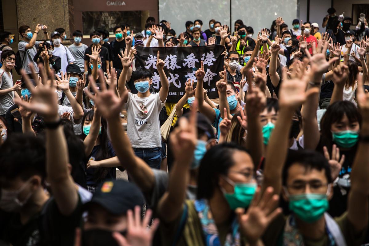 參加7.1遊行香港市民無懼國安法,展開「光復香港 時代革命」橫幅,做「五大訴求 缺一不可」手勢。(DALE DE LA REY/AFP)