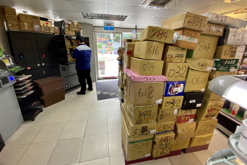 台灣疫情升溫,消費者減少到公共場所購物,以減少接觸來降低感染機率,線上購物成為防疫新選擇。30 日一家便利商店內待取貨的包裹已經快堆到天花板了。(中央社)