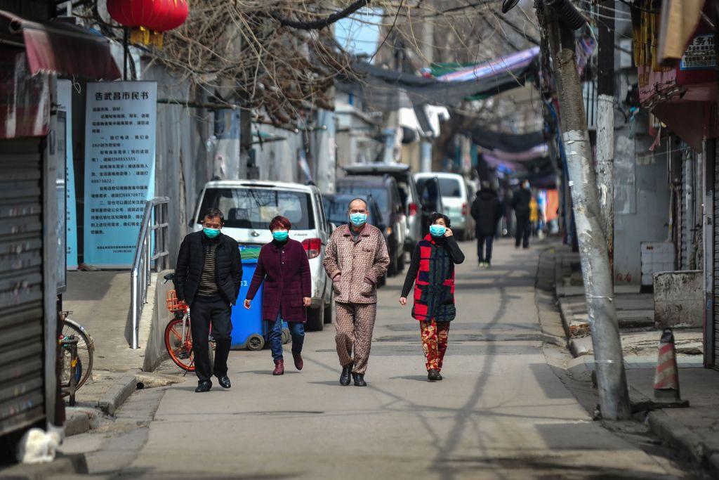 圖為2020年3月4日武漢居民佩戴口罩在街頭行走。(Photo by STR/AFP via Getty Images)