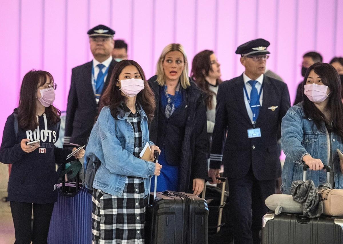 中共肺炎(俗稱武漢肺炎、新冠肺炎)已經在中國所有省份蔓延,並在全球開始傳播。越來越多的全球航空公司。圖為戴著口罩抵達洛杉磯國際機場的旅客。(MARK RALSTON/AFP via Getty Images)