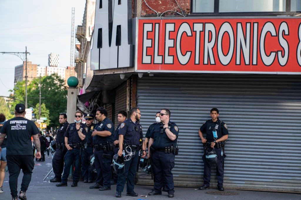 2020年6月4日,紐約市警察在紐約市布朗士區的零售店和餐館中心前面執勤。(David Dee Delgado/Getty Images)