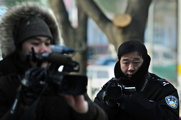 港媒1月12日報道說,中共當局起草的官方文件證實,紐約市警察局「大規模」使用海康威視的監控產品。圖為2009年12月25日,一名中共警察在法院外對等候法庭審判結果的記者偷偷錄像。(FREDERIC J. BROWN/AFP/Getty Images)