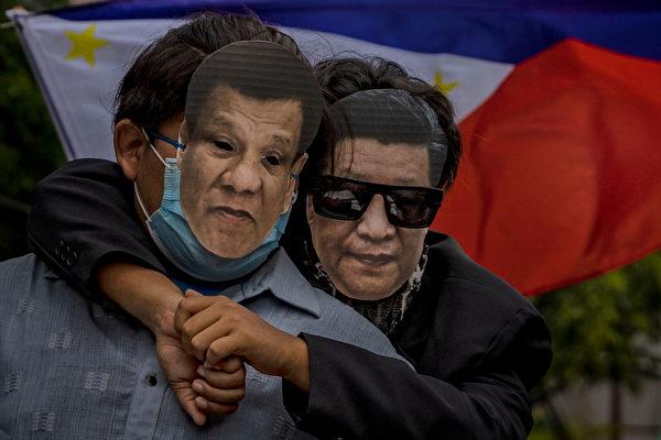 6月12日,菲律賓民眾戴著習近平和菲律賓總統杜特蒂的面具,在中共駐馬尼拉使館前抗議中共強佔菲律賓水域。(Ezra Acayan/Getty Images)