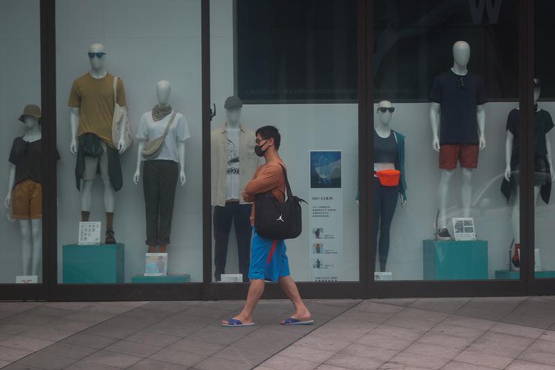 目前台灣疫情警戒第三級到6月14日,行政院7日宣佈延長全國三級警戒管制為期兩周至6月28日,全國各級學校也配合停止到校上課至暑假。圖為台北市信義商圈街頭冷清,人潮較以往少,民眾戴口罩上街。(中央社)