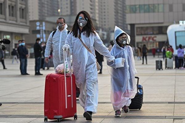 2020年4月8日,湖北武漢,武漢火車站外準備搭車的民眾全副武裝。(HECTOR RETAMAL/AFP via Getty Images)