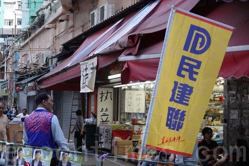 2019年11月24日,香港舉行區議會選舉,土瓜灣長毛和民建聯主席對決,民建聯在一間結束舖頭前打告急牌。(余鋼/大紀元)