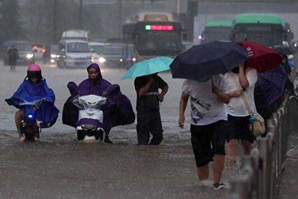 2021年7月20日,河南省鄭州市,暴雨造成街道嚴重淹水,電單車與行人涉水而行。(STR/AFP via Getty Images)