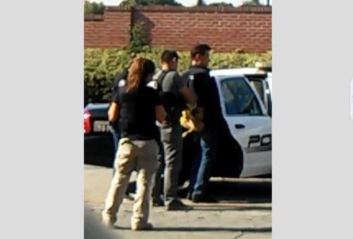 射殺謝一寧的疑犯在周圍工人目睹下被戴上手銬、押入警車。(目擊者提供)