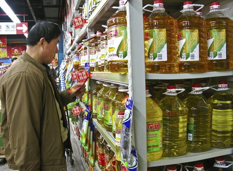 大陸食油漲價。圖為一北京市民在超市選購食用油。(TEH ENG KOON/AFP/Getty Images)