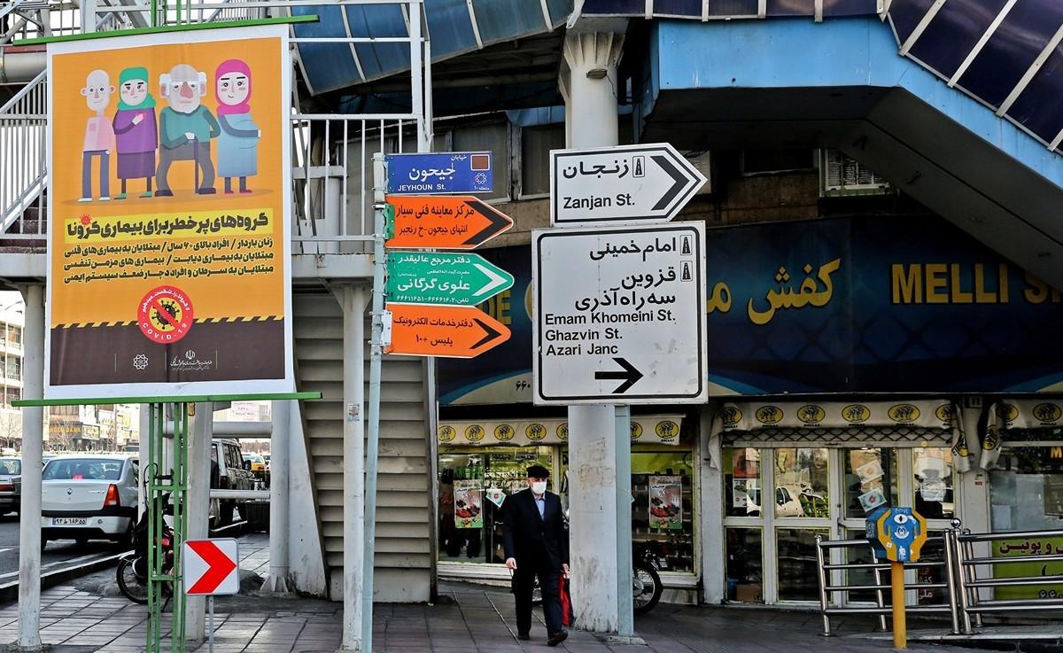 一名戴著防護口罩的伊朗人從德黑蘭大街上豎起的武漢肺炎防疫宣傳畫旁經路過。攝於2020年3月4日。(ATTA KENARE/AFP)