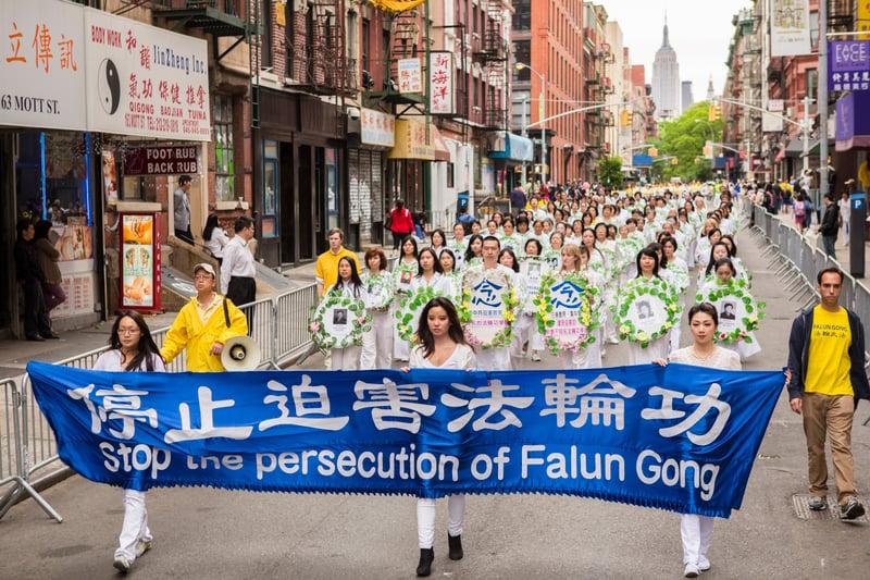 在海外的遊行隊伍中,法輪功學員手持花圈悼念在中國大陸被迫害致死的法輪功學員。(明慧網)