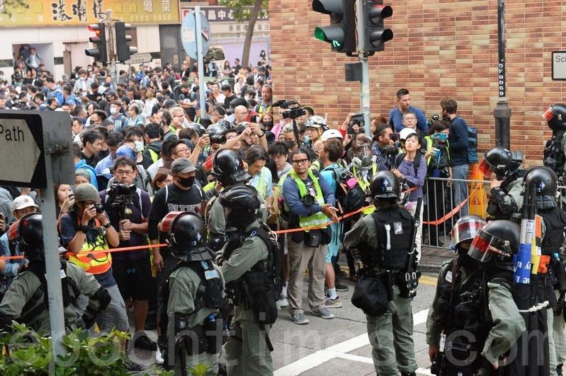 2019年11月25日,防暴警察封鎖往理大的外圍科學館徑,與趕來救助理大留守者的新科區議員和抗爭者對峙。(宋碧龍/大紀元)