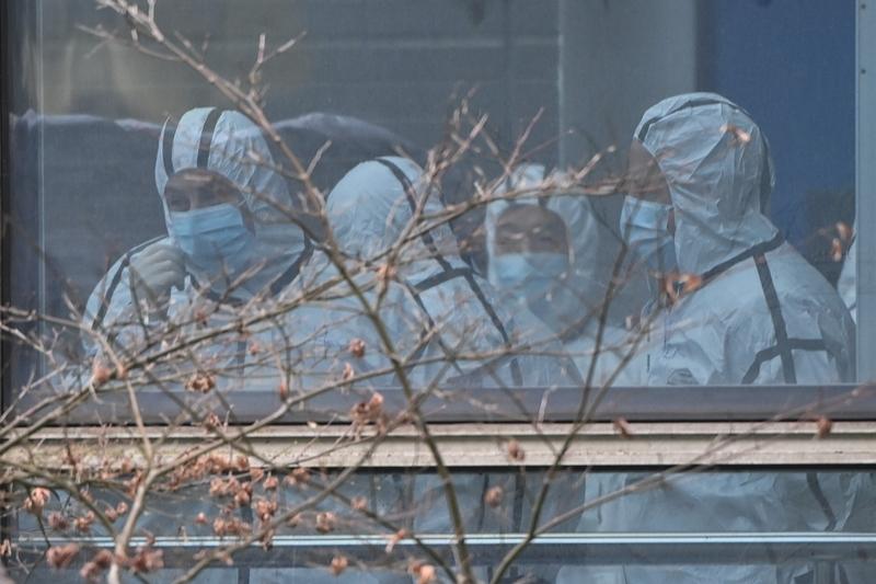 2021年2月2日,世衛專家小組的成員穿著防護服參觀湖北省動物疾病預防控制中心,調查中共病毒的起源。(HECTOR RETAMAL/AFP via Getty Images)