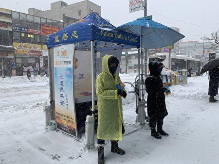 法輪功學員頂風冒雪,堅持每天向過往的民眾傳遞法輪大法好的福音。(林丹/大紀元)