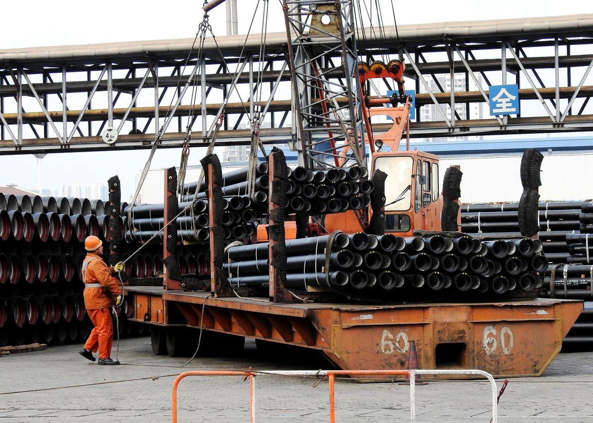 圖為中國江蘇,一名工人正在裝運鋼管。(STR/AFP/Getty Images)