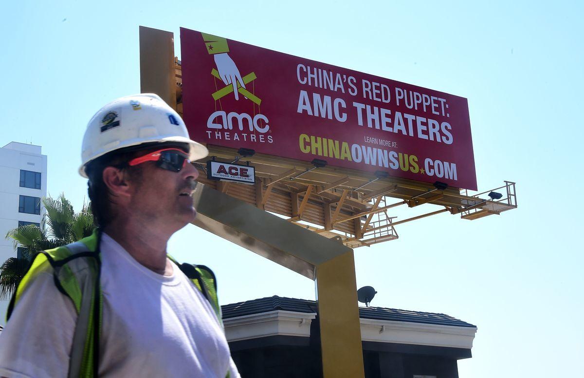 中國大連萬達集團5月23日宣佈已基本出清美國連鎖電影院線公司AMC的全部股份,並退出董事會。圖為美國荷里活著名的日落地帶沿線的廣告牌,批評AMC被中共控制。(FREDERIC J. BROWN/AFP)