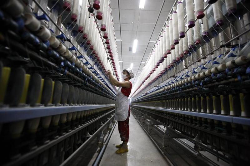 有學者預計,受貿易戰影響,中國明年GDP增長會更差。圖為淮北一家紡織廠。(AFP)