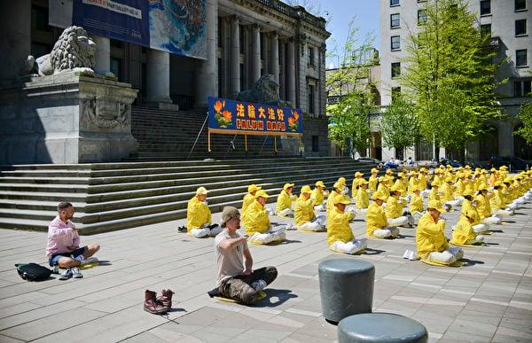 2021年5月2日,溫哥華部份法輪功學員在市中心的藝術館前煉功,慶祝法輪大法日,幾位路過的西人也在一旁學煉起來。(大宇/大紀元)