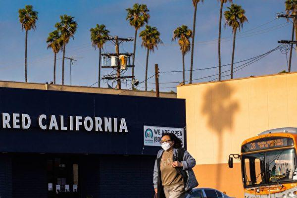 4月初在洛杉磯,一名戴口罩的婦女走過街頭。 (APU GOMES/AFP via Getty Images)
