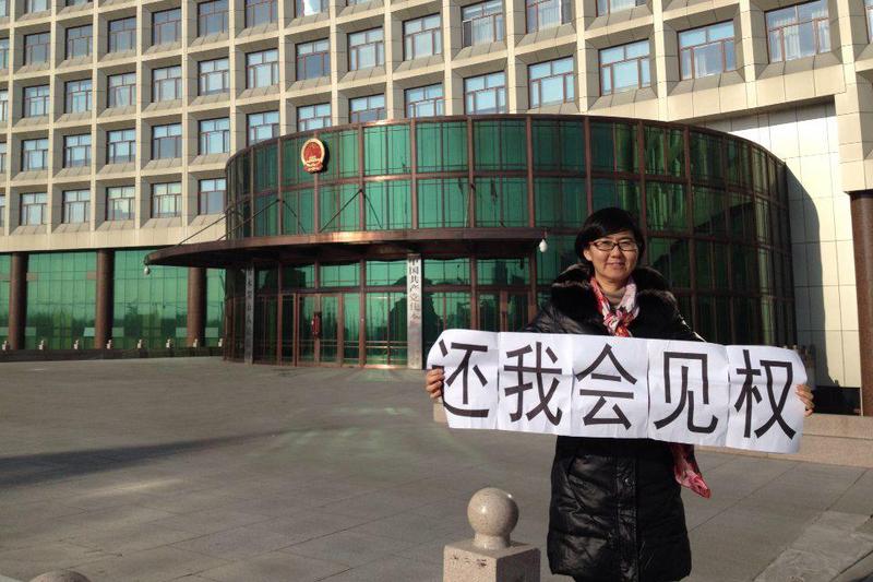 建三江法輪功學員被非法庭審,代理律師要求會見遭到拒絕,王宇律師舉牌抗議。(大紀元資料室)