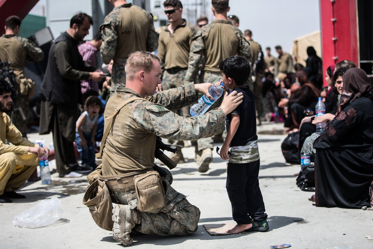 五角大樓證實,美軍開始從喀布爾機場撤出。圖為2021年8月20日,阿富汗喀布爾(Kabul),美軍士兵拿水給一位阿富汗兒童喝。(Samuel Ruiz/US Central Command Public Affairs/AFP)