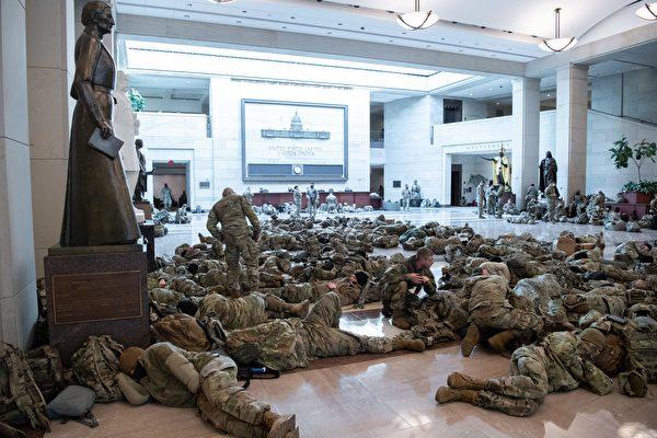 2021年1月13日,國民警衛隊成員躺在華盛頓國會山的國會遊客中心休息,眾議院當天辯論並投票,彈劾美國總統唐納德·特朗普。( SAUL LOEB/AFP via Getty Images)