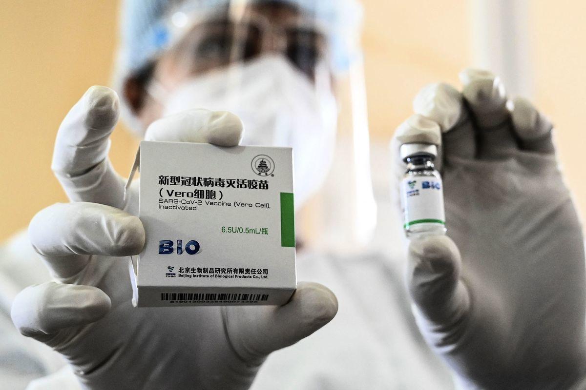 一名醫護人員展示中國產疫苗。(ISHARA S. KODIKARA/AFP via Getty Images)