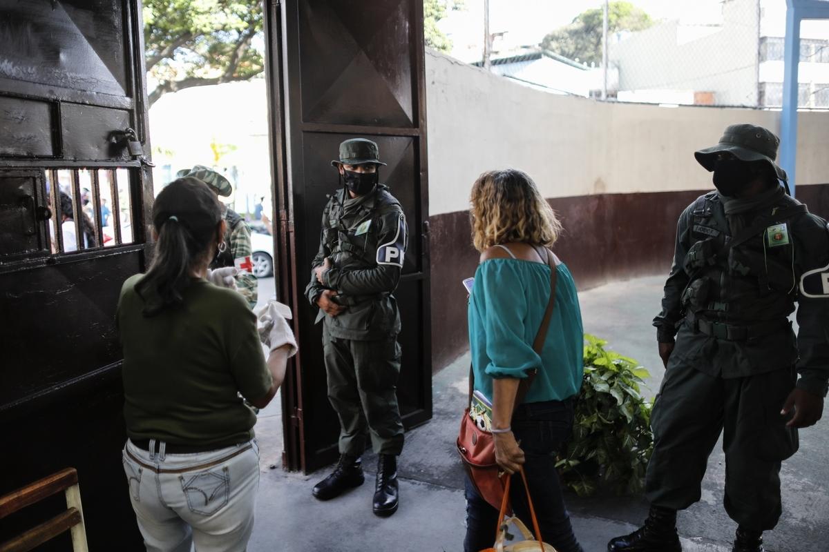 委內瑞拉周日進行國民議會選舉,然而該國反對派聯盟表示,這場選舉是馬杜羅企圖掌管國會的舞弊行動。圖為選舉期間站崗的軍隊和民兵人員。(Leonardo Fernandez Viloria/Getty Images)