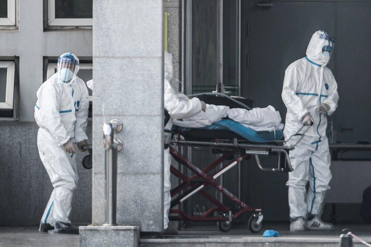 2020年1月18日,身著防護裝備的醫護人員把患者推入武漢金銀潭醫院。(STR/AFP via Getty Images)