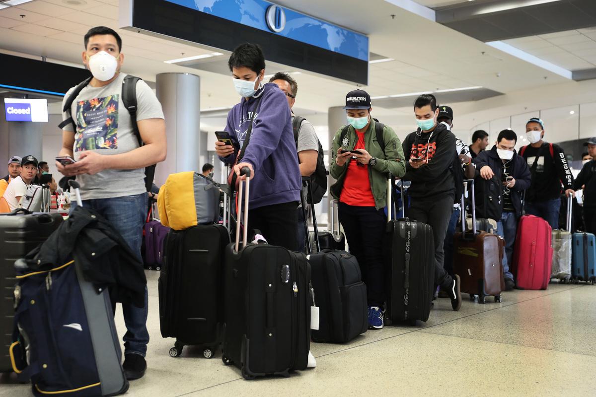 據彭博社統計,在疫情期間,全球航空業恐有40萬人失業或工作不保。圖為2020年3月15日,在佛羅里達州邁阿密國際機場,人們戴著口罩等待辦理登機手續。(Joe Raedle/Getty Images)
