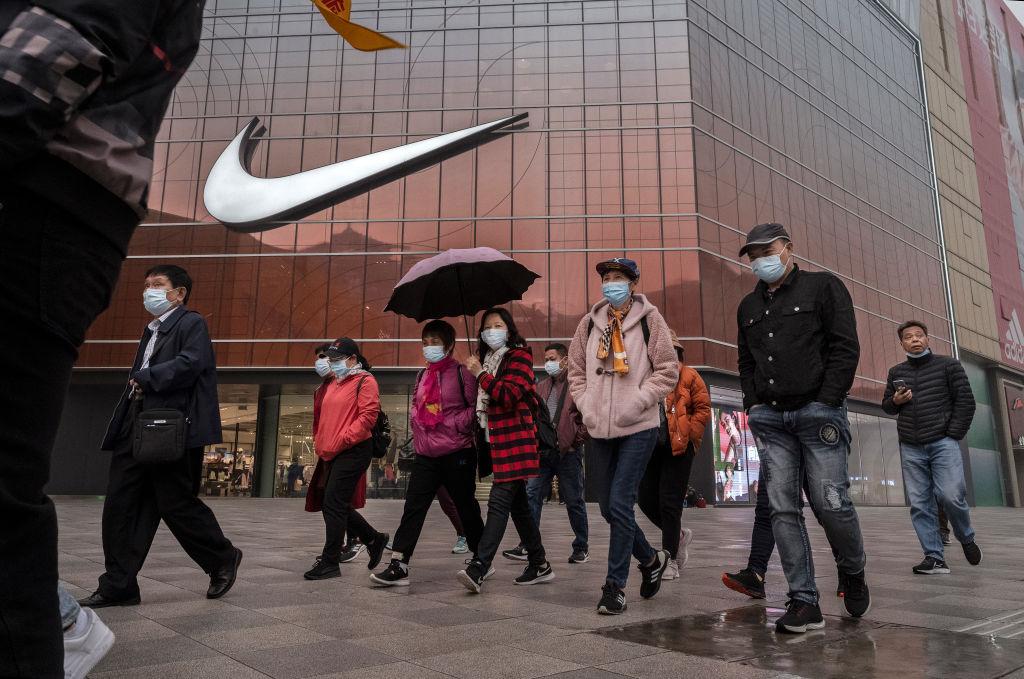 中共官媒煽動的抵制西方品牌運動,僅僅幾天又出現疑似「降溫」跡象。圖為2021年3月26日,北京一家Nike商店門前的行人。(Kevin Frayer/Getty Images)